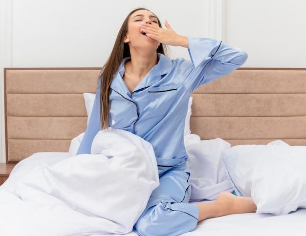 Jonge, mooie vrouw in blauwe pyjama die op bed zit en wakker wordt met ochtendmoeheid en geeuwen in het interieur van de slaapkamer bedroom