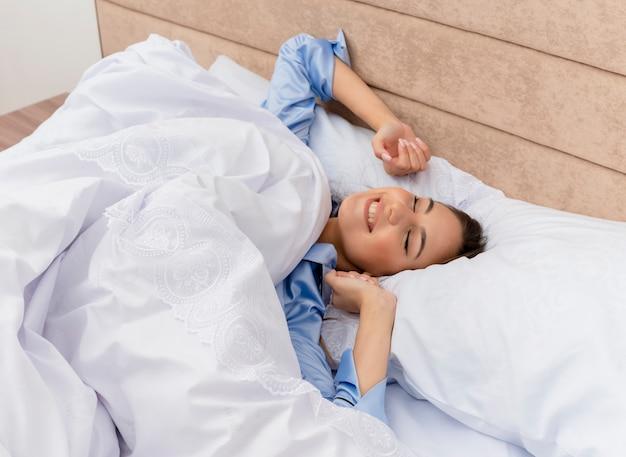 Jonge mooie vrouw in blauwe pyjama liggend op bed rusten op zachte kussens wakker haar handen in slaapkamer interieur op lichte achtergrond uitrekken