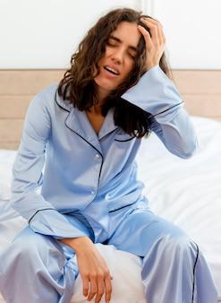 Jonge mooie vrouw in blauwe pyjama's tot op bed