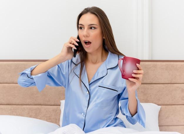 Jonge mooie vrouw in blauwe pyjama zittend op bed met kopje koffie praten op mobiele telefoon wordt verbaasd in slaapkamer interieur op lichte achtergrond
