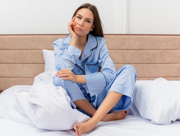 Jonge mooie vrouw in blauwe pyjama zittend op bed ontevreden in slaapkamer interieur