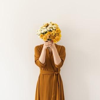 Jonge mooie vrouw in bruine jurk met boeket van wilde bloemen tegen witte muur.