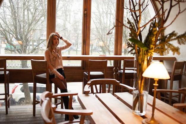 Jonge mooie vrouw in café. grunge. meisje in een café in een beige blouse. jong meisje in een coffeeshop in zwarte korte broek en een beige blouse met lang krullend haar.