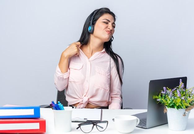 Jonge mooie vrouw in casual kleding met koptelefoon en microfoon die er geïrriteerd en geïrriteerd uitziet zittend aan de tafel met laptop over witte muur die op kantoor werkt