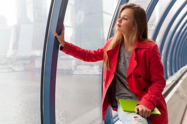 Jonge mooie vrouw in casual outfit met tablet laptop in stedelijk gebouw, het dragen van jeans, roze trenchcoat, zittend bij raam met uitzicht op de stad