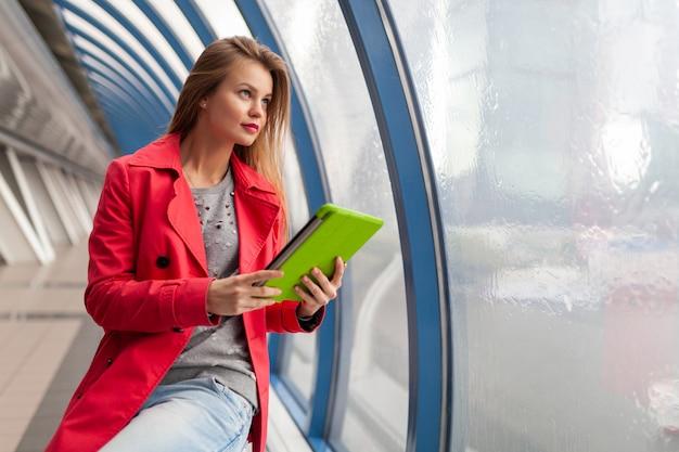 Jonge mooie vrouw in casual outfit tablet laptop houden in stedelijk gebouw, het dragen van jeans, roze trenchcoat, bij raam met uitzicht op de stad, onderwijs online