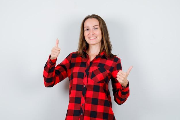 Jonge mooie vrouw in casual shirt duimen opdagen en op zoek zalig, vooraanzicht.