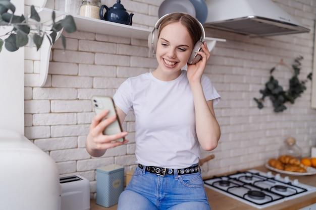 Jonge, mooie vrouw in casual zit op de keukentafel met een koptelefoon en maakt videocall Premium Foto