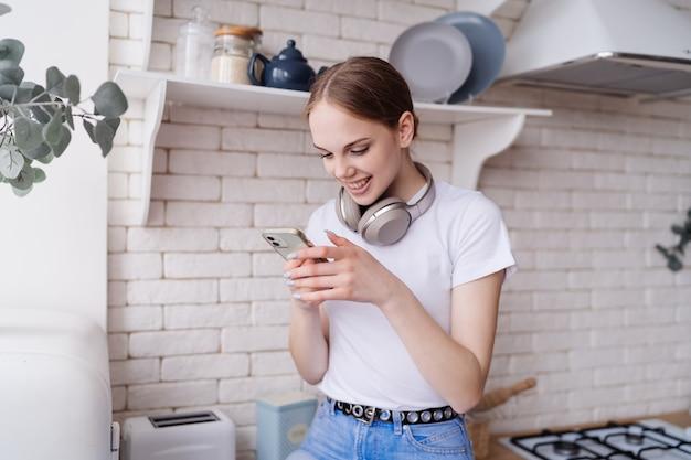Jonge, mooie vrouw in casual zit op de keukentafel met een koptelefoon en maakt videocall