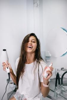 Jonge mooie vrouw in de badkamer met een haardroger en een kleine fles, dichtbij bekeken