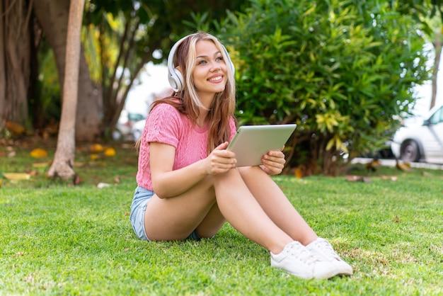 Jonge mooie vrouw in de buitenlucht die muziek luistert met de mobiel en gelukkig