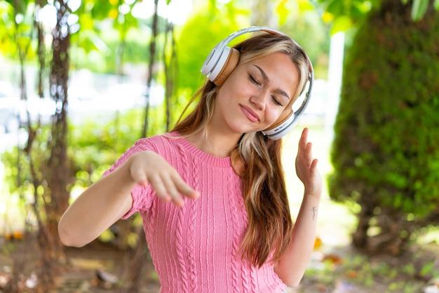 Jonge mooie vrouw in de buitenlucht luisteren naar muziek en dansen