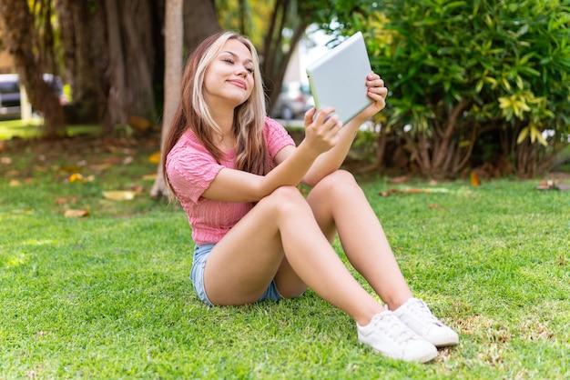Jonge mooie vrouw in de buitenlucht met een tablet
