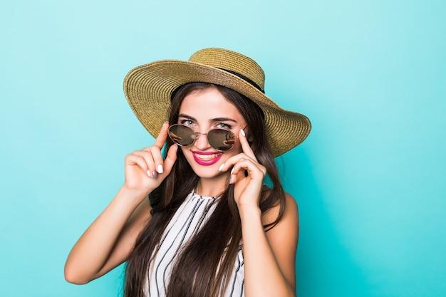 Jonge mooie vrouw in de hoed van de zomerkleren en zonnebril op turkooise achtergrond