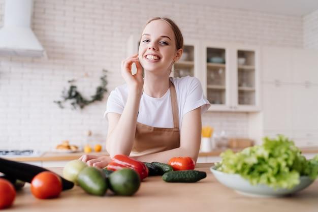 Jonge mooie vrouw in de keuken in een schort en verse groenten op tafel