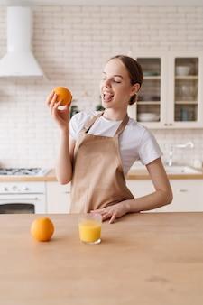 Jonge mooie vrouw in de keuken in een schort, fruit en jus d'orange