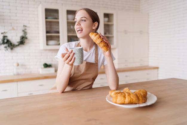 Jonge mooie vrouw in de keuken in een schort met koffie en croissant geniet van haar ochtend