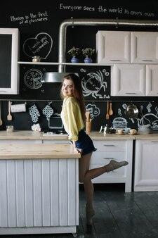 Jonge mooie vrouw in de keuken thuis