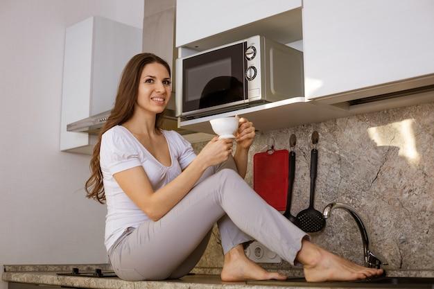 Jonge mooie vrouw in de keuken zitten aan de tafel met een mok in haar hand glimlachen