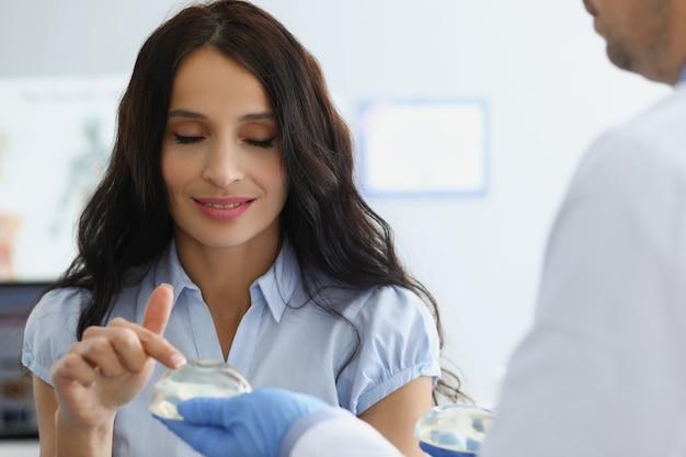 Jonge mooie vrouw in de kliniek kiest een borstimplantaat. chirurg arts raadpleegt een patiënt over mammoplastiek van de borst