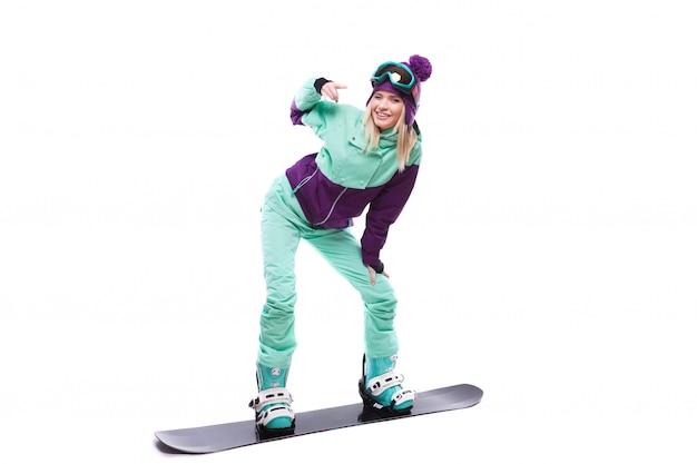 Jonge mooie vrouw in de paarse rit van het skikostuum snowboard