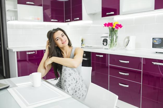 Jonge mooie vrouw in de vroege ochtend die koffie op de keuken heeft. frisse ochtend. bracing drankje. vergoedingen voor werk. wakker dame.