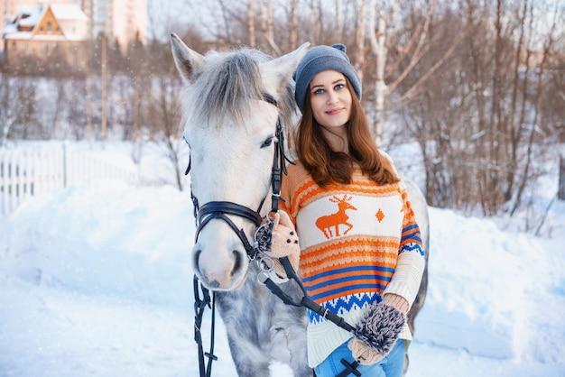 Jonge mooie vrouw in de winter met mooi wit paard