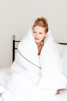 Jonge mooie vrouw in deken op bed, wordt 's ochtends wakker