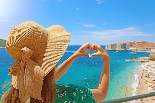 Jonge mooie vrouw in dubrovnik handen gevormd hart maken op warme zonnige lente zomer. meisje met hoed gelukkig buitenshuis in haar reis in zuid-kroatië, europa.