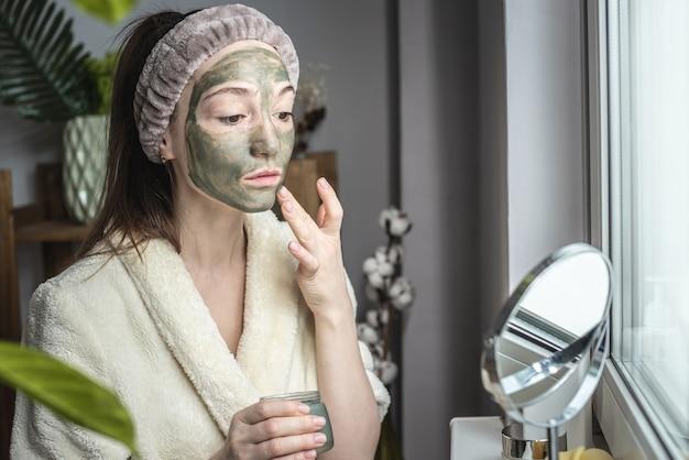 Jonge, mooie vrouw in een badjas met dressing brengt een groen cosmetisch masker op haar gezicht aan