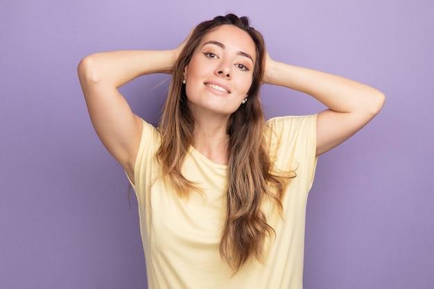 Jonge, mooie vrouw in een beige t-shirt die naar de camera kijkt, blij en positief glimlachend, zelfverzekerd over paars