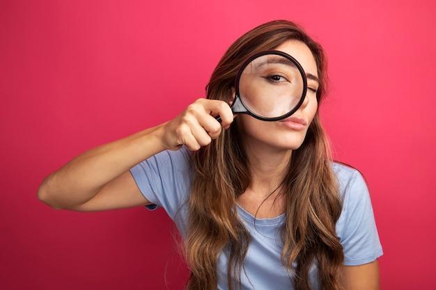 Jonge, mooie vrouw in een blauw t-shirt die door een vergrootglas naar de camera kijkt met belangstelling voor roze