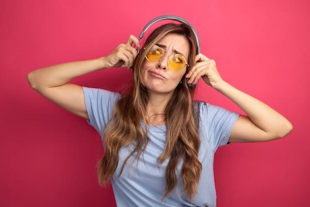 Jonge, mooie vrouw in een blauw t-shirt met een gele bril met een koptelefoon die er verward uitziet over een roze achtergrond