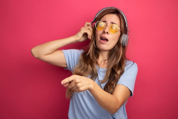 Jonge, mooie vrouw in een blauw t-shirt met een gele bril met een koptelefoon die opzij kijkt, verward met de wijsvinger naar de zijkant wijst