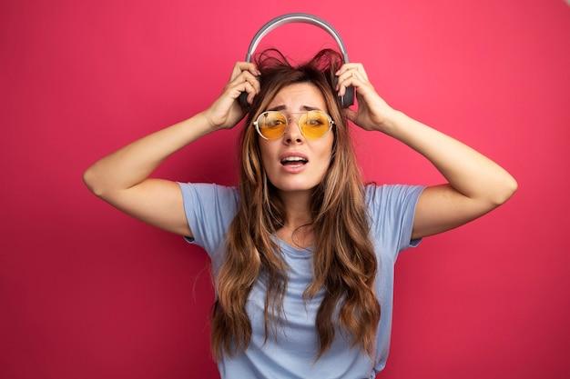 Jonge, mooie vrouw in een blauw t-shirt met een gele bril met een koptelefoon die verward en teleurgesteld naar de camera kijkt