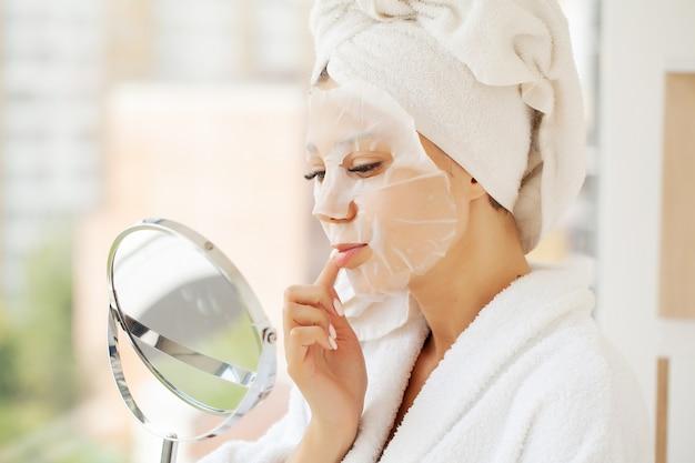 Jonge mooie vrouw in een gezichtsmasker, huidzorg.
