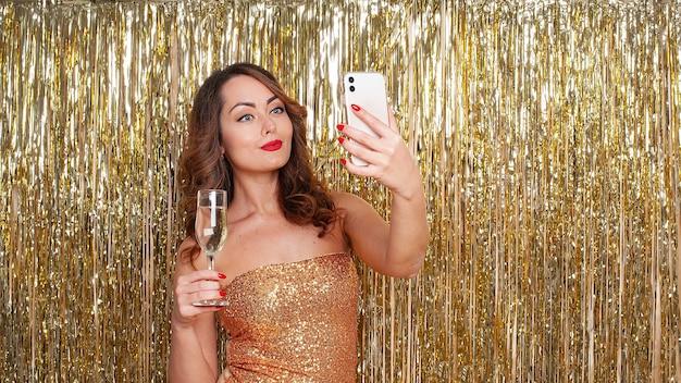 Jonge mooie vrouw in een gouden jurk champagne drinkt, maakt een selfie op een smartphone, plezier op een feestje op een glanzende gouden achtergrond