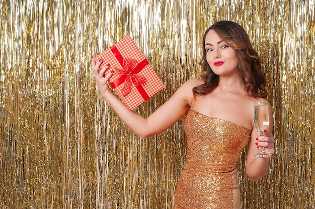 Jonge mooie vrouw in een gouden jurk drinkt champagne, met een rode geschenkdoos, plezier op een feestje op een glanzende gouden achtergrond