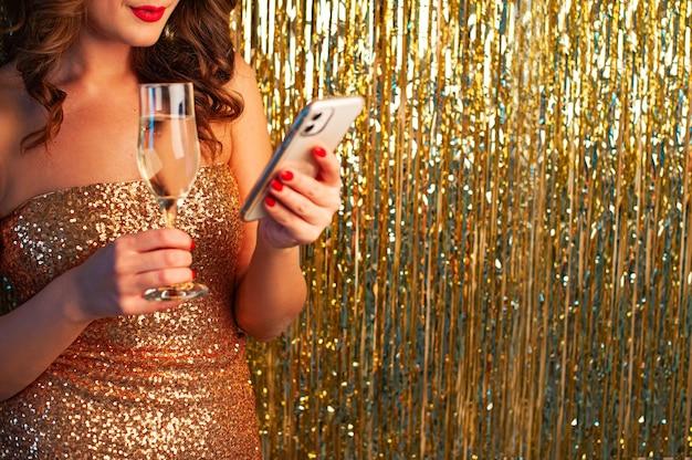 Jonge mooie vrouw in een gouden jurk drinkt champagne, met een smartphone, plezier op een feestje op een glanzende gouden achtergrond