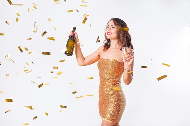 Jonge mooie vrouw in een gouden jurk drinkt champagne, plezier op een feestje met gouden confetti op een witte achtergrond