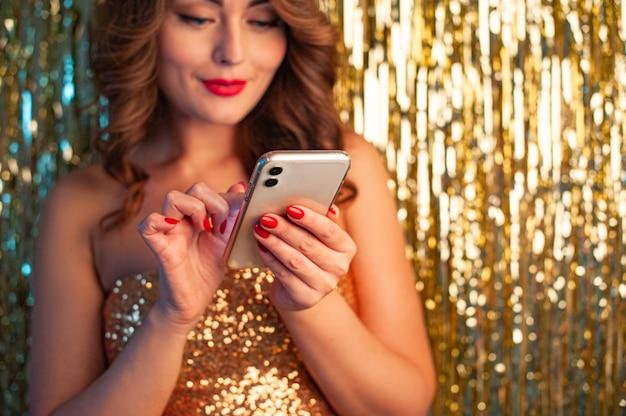 Jonge mooie vrouw in een gouden jurk met behulp van telefoon plezier op een feestje op een glanzende gouden achtergrond