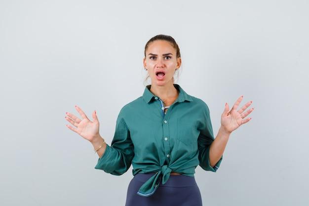 Jonge, mooie vrouw in een groen shirt die een overgavegebaar toont en er bang uitziet, vooraanzicht.