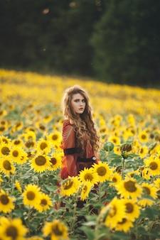 Jonge mooie vrouw in een jurk onder bloeiende zonnebloemen. agro-cultuur.