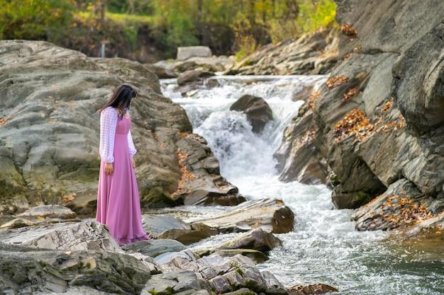 Jonge mooie vrouw in een lange modieuze jurk die in de buurt van een kleine bergrivier staat met snel stromend water.