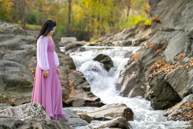 Jonge mooie vrouw in een lange roze modieuze jurk die in de buurt van een riviertje staat met snel stromend water.