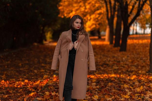 Jonge mooie vrouw in een modieuze beige jas en trui wandelt in de natuur met fel oranje herfstblad