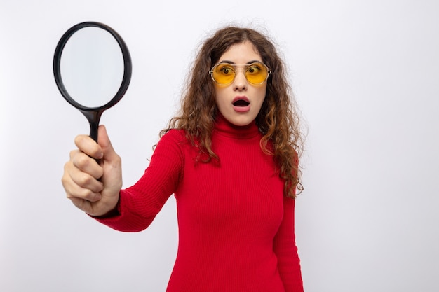 Jonge, mooie vrouw in een rode coltrui met een gele bril die een vergrootglas vasthoudt en ernaar kijkt verbaasd en verrast terwijl ze op wit staat