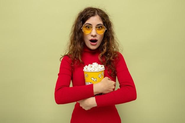 Jonge, mooie vrouw in een rode coltrui met een gele bril met een emmer popcorn verbaasd en verrast terwijl ze op groen staat