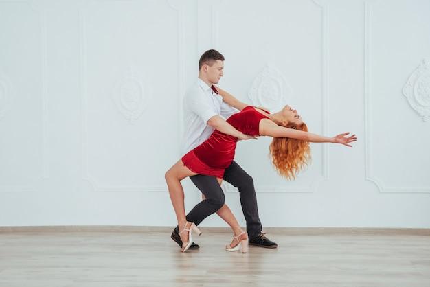 Jonge mooie vrouw in een rode kleding en man dansen geïsoleerd op een witte achtergrond.