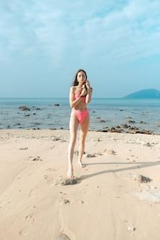 Jonge mooie vrouw in een roze badpak staat op een zandstrand